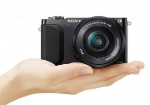 NEX-3N held in the palm of a hand.